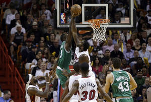 Photo - Boston Celtics small forward Jeff Green (8) is blocked by Miami Heat center Greg Oden (20) during the second quarter of an NBA basketball game in Miami, Tuesday, Jan. 21, 2014. (AP PhotoAlan Diaz)