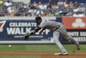Photo - Chicago White Sox shortstop Alexei Ramirez tries, but fails, to grab a ball thrown by first baseman Adam Dunn during the fourth inning of the baseball game against the New York Yankees at Yankee Stadium Monday, Sept. 2, 2013 in New York. Dunn was charged with a throwing error. (AP Photo/Seth Wenig)