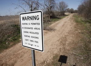 Photo - A sign warning people of the potential for hunters seen last month at the Stinchcomb Wildlife Refuge near Lake Overholser in Oklahoma City. A proposed new ordinance would allow bow hunting for deer in October if approved. <strong>PAUL HELLSTERN - The Oklahoman</strong>