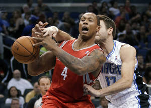 Photo -   Houston Rockets' Greg Smith (4) loses the ball as he is fouled by Orlando Magic's Josh McRoberts (17) during the first half of an NBA preseason basketball game, Friday, Oct. 26, 2012, in Orlando, Fla. (AP Photo/John Raoux)