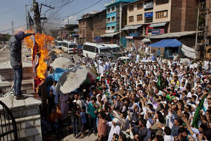 "Photo -   A Kashmiri Muslim with his face covered burns a mock American flag as others shout slogans during a protest in Srinagar, India, Friday, Sept. 14, 2012. The protest was held against an anti-Islam film called ""Innocence of Muslims"" that ridicules Islam's Prophet Muhammad. (AP Photo/Dar Yasin)"