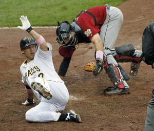 Photo -   Pittsburgh Pirates' Clint Barmes, left, scores from second base past Houston Astros catcher Jason Castro with the game-winning run on a hit by Josh Harrison in the 12th inning of the baseball game on Sunday, May 13, 2012, in Pittsburgh. The Pirates won 3-2. (AP Photo/Keith Srakocic)