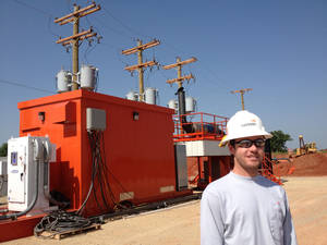 Photo - Jarod Tracy, production engineer for Devon Energy Corp., stands in front of a prototype General Electric generator southwest of Stillwater. The generator runs on natural gas in a part of northern Oklahoma's Mississippian oil play where utility power is not available. <strong> - provided</strong>