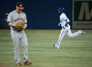 Photo - Toronto Blue Jays Jose Bautista, right, rounds the bases past Houston Astros starting pitcher Brett Oberholtzer, left, after hitting a solo home run during the first inning of the MLB American League baseball game in Toronto on Tuesday, April 8, 2014. (AP Photo/The Canadian Press, Nathan Denette)