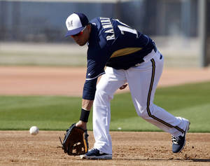 Photo - Milwaukee Brewers third baseman Aramis Ramirez fields grounders during a spring training baseball practice, Saturday, Feb. 22, 2014, in Phoenix. (AP Photo/Rick Scuteri)