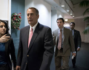 "Photo - Speaker of the House John Boehner, R-Ohio, walks to a closed-door GOP caucus as Congress meets to negotiate a legislative path to avoid the so-called ""fiscal cliff"" of automatic tax increases and deep spending cuts that could kick in Jan. 1., at the Capitol in Washington, Sunday, Dec. 30, 2012. (AP Photo/J. Scott Applewhite)"