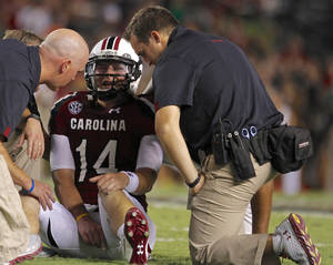 Photo -   South Carolina quarterback Connor Shaw (14) is tended to by the South Carolina training staff during the first half of an NCAA college football game against UAB at Williams-Brice Stadium in Columbia, S.C., Saturday, Sept. 15, 2012. (AP Photo/Brett Flashnick)