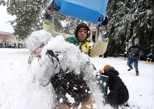 Photo - University of Oregon football player Pharaoh Brown, center, dumps a tub load of snow on fellow student Charley Gibson during a snow battle involving hundreds of students on campus Friday, Dec. 6, 2013. (AP Photo/The Register-Guard, Chris Pietsch)