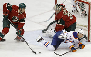 Photo - Minnesota Wild defenseman Clayton Stoner, left, clears a rebound as Wild goalie Darcy Kuemper (35) covers the net and Edmonton Oilers right wing Jordan Eberle (14) falls during the first period of an NHL hockey game in St. Paul, Minn., Thursday, Jan. 16, 2014. (AP Photo/Ann Heisenfelt)