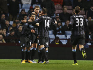 photo - Manchester City's Carlos Tevez, left, runs to celebrate with his teammates after scoring against Aston Villa during their English Premier League soccer match at the Villa Park ground in Birmingham, England, Monday, March 4, 2013. (AP Photo/Lefteris Pitarakis)