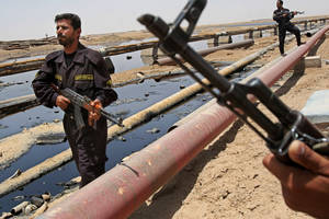 Photo - FILE - In this June 22, 2008 file photo, Iraqi police officers protecting oil installations secure an oil pipeline from the Rumailah refinery, north of Basra, Iraq. The turmoil in Iraq has thrown the OPEC member's ambitious plans to boost oil production into doubt, threatening to crimp its most vital economic lifeline. Northern oil fields imperiled by the militants' advance have been shut down, and companies have begun evacuating workers elsewhere in the country. Iraq's Kurdish minority has moved to solidify control over the northern oil-rich city of Kirkuk and other disputed areas, weakening Baghdad's claims to the energy riches buried beneath while bolstering the Kurds' aspirations of greater autonomy. (AP Photo/Nabil al-Jurani, File)