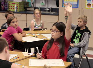 Photo - Fifth grader Emma Carlson raises a hand in class at Russell Babb Elementary School in Harrah , Wednesday, August 28, 2013. For an exploration of an upcoming bond issue for Harrah schools.Photo by David McDaniel, The Oklahoman