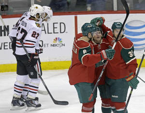 Photo - Minnesota Wild's Matt Cooke, right center, is congratulated on his goal by Marco Scandella and Nate Prosser, right, as Chicago Blackhawks' Johnny Oduya, left, of Sweden, and Michal Rozsival, skate to their bench in the first period of an NHL hockey game, Thursday, Jan. 23, 2014, in St. Paul, Minn. (AP Photo/Jim Mone)