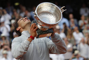 Photo - Spain's Rafael Nadal lifts up his cup after defeating Serbia's Novak Djokovic in their final match of  the French Open tennis tournament at the Roland Garros stadium, in Paris, France, Sunday, June 8, 2014. Nadal won 3-6, 7-5, 6-2, 6-4. (AP Photo/Michel Euler)