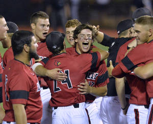 Photo - Louisville's Nick Solak, center right, hugs teammate Logan Taylor after the team's 7-4 victory over Kennesaw State to win the NCAA college baseball tournament Louisville super regional game in Louisville, Ky., Saturday, June 7, 2014. (AP Photo/Timothy D. Easley)