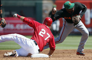 Photo - San Francisco Giants' Ehire Adrianza, right, throws to first base after forcing out Los Angeles Angels' Mike Trout (27) in the first inning of a spring training baseball game, Monday, March 17, 2014, in Tempe, Ariz. (AP Photo/Ross D. Franklin)