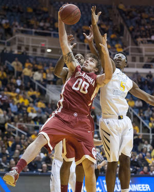 Photo - Oklahoma's Ryan Spangler,  front left, battles West Virginia's Devin Williams for a rebound during the second half of an NCAA college basketball game on Wednesday, Feb. 5, 2014, in Morgantown, W.Va. West Virginia won 91-86 in overtime. (AP Photo/Andrew Ferguson)