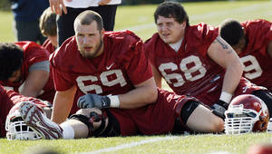 Photo - COLLEGE FOOTBALL: Lane Johnson (69) and Bronson Irwin (68) stretch during spring football practice for the OU Sooners on the campus of the University of Oklahoma in Norman, Okla., Monday, March 5, 2012. Photo by Nate Billings, The Oklahoman