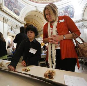 Photo - Alex Harvey, 11, and his mentor Melynda Stone look at a piece of baleen from a whale at The State Capitol in Oklahoma City, Wednesday January 15, 2014. <strong>GOOCH - STEVE GOOCH</strong>