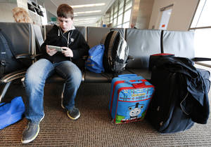 photo - Nicholas Lintz, 14, waits for a flight to Orlando, Fla., at Will Rogers World Airport in Oklahoma City. Lintz is on spring break and going to Disney World with his family. Photo by Steve Gooch, The Oklahoman