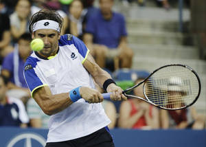 Photo - David Ferrer, of Spain, returns a shot to Janko Tipsarevic, of Serbia, during the fourth round of the 2013 U.S. Open tennis tournament, Monday, Sept. 2, 2013, in New York. (AP Photo/David Goldman)