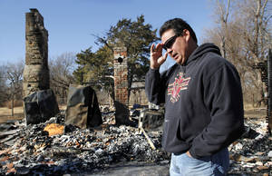 photo - Chris Cochran walks through the charred rubble that was his family's home in a rural area near Cashion until it was destroyed in a recent fire. His son, Cayden, a star player when he attended Cashion, will quarterback Valdosta State in the Division II national championship game on Saturday.  Photo by Jim Beckel, The Oklahoman