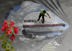 "Photo - FILE - In this April 8, 2014, file photo a school utility worker mops a mural depicting the missing Malaysia Airlines Flight 370 at the Benigno ""Ninoy"" Aquino High School campus at Makati city east of Manila, Philippines. After the shooting down of Malaysia Airlines Flight 17 on Thursday, July 17, 2014, Malaysia is now grappling with the horrific loss of two of its airplanes, just four months apart. (AP Photo/Bullit Marquez, File)"