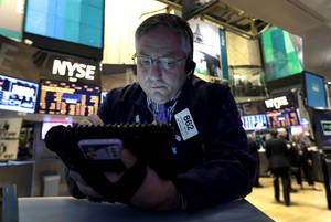Photo - FILE - In this New York Stock Exchange Friday, Dec. 21, 2012, photo, Trader Warren Meyers uses his handheld device as he works on the floor of the New York Stock Exchange. Stocks are down Monday, Dec. 24, 2012, amid concern that lawmakers will fail to reach a deal to stop the U.S. going over the so-called fiscal cliff. (AP Photo/Richard Drew)