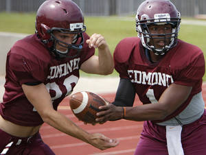 Photo - Edmond Memorial quarterback Kameron Doolittle hands the ball off to running back Cale Olbert during spring football practice. PHOTO BY CHRIS LANDSBERGER, THE OKLAHOMAN
