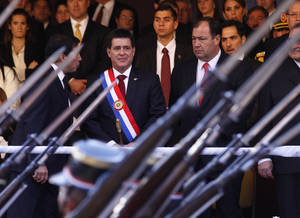 Photo - In this Aug.15, 2013 photo, Paraguay's President Horacio Cartes, center, and Vice President Juan Afara, right, attend a military parade in Asuncion, Paraguay. Cartes wants open-ended, blanket approval to send troops to the northern department of San Pedro against the Paraguayan People's Army without having to declare a state of emergency. The government blames the guerrilla group for the recent deaths of five farmhands. Human rights groups fear the step, but Cartes has plenty of support. House approval was expected Wednesday night, Aug. 21, 2013, before a Senate vote Thursday afternoon. (AP Photo/ Cesar Olmedo)