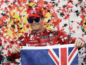 Photo - FILE - In this Oct. 5, 2013, file photo, Scott Dixon, of New Zealand, celebrates after winning the first IndyCar Grand Prix of Houston auto race in Houston. Much has changed since Dixon wrapped up his third IndyCar championship five months ago. He's got a new engine manufacturer in Chevrolet, and longtime teammate Dario Franchitti has retired and been replaced by Target Chip Ganassi Racing with Indianapolis 500 winner Tony Kanaan. (AP Photo/David J. Phillip, File)