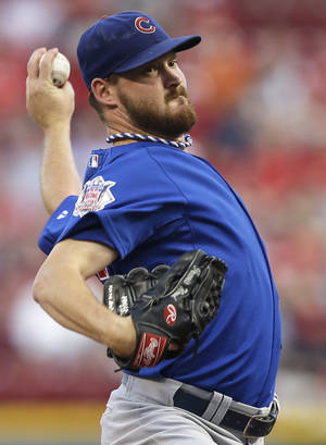 Photo - Chicago Cubs starting pitcher Travis Wood throws against the Cincinnati Reds in the first inning of a baseball game, Monday, Sept. 9, 2013, in Cincinnati. (AP Photo/Al Behrman)