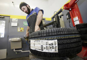 Photo - In this Feb. 12, 2014 photo, Lonn Schubert installs a Goodyear tire on a rim in South Euclid, Ohio. Goodyear reports quarterly earnings on Tuesday, April 29, 2014.  (AP Photo/Tony Dejak)
