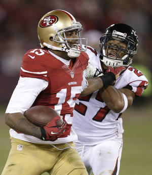 Photo - San Francisco 49ers wide receiver Michael Crabtree (15) stiff-arms Atlanta Falcons cornerback Robert McClain during the second half of an NFL football game in San Francisco, Monday, Dec. 23, 2013. (AP Photo/Tony Avelar)