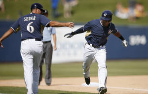 Photo - Milwaukee Brewers' Khris Davis, right, celebrates his home run against the San Francisco Giants with third base coach Ed Sedar (6) during the fifth inning of a spring exhibition baseball game, Tuesday, March 25, 2014, in Phoenix. (AP Photo/Ross D. Franklin)