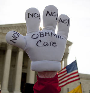 Photo -   FILE - This March 28, 2012 file photo shows Janis Haddon,of Atlanta, holding a glove with a message outside the Supreme Court in Washington as the court concluded three days of hearing arguments on the constitutionality of President Barack Obama's health care overhaul. America's health care system is unsustainable. It's not one problem, but three combined: high cost, uneven quality and millions uninsured. Major changes will keep coming. Every family will be affected. (AP Photo/Carolyn Kaster, File)