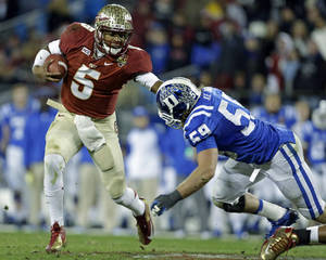 Photo - FILE - In this file photo from Dec. 7, 2013, Florida State's Jameis Winston (5) scrambles as Duke's Kelby Brown (59) defends in the first half of the Atlantic Coast Conference Championship NCAA football game in Charlotte, N.C. The No. 1-ranked Florida State held their final workout on campus Monday, Dec. 30 2013, before flying to California to face No. 2 Auburn in the BCS NCAA college football championship game. (AP Photo/Bob Leverone, file)