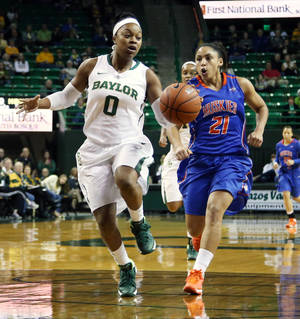Photo - Baylor guard Odyssey Sims (0), left, drives past Houston Baptist guard Rachel Arthur (21), right, in the first half of an NCAA college basketball game, Sunday, Dec. 15, 2013, in Waco, Texas. (AP Photo/The Waco Tribune Herald, Rod Aydelotte)