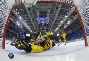 Photo - Goalkeeper Jennifer Harss of Germany reaches for the puck as Johanna Olofsson's of Sweden shot get by her for a goal during the third period of women's ice game at Shayba Arean during the 2014 Winter Olympics, Tuesday, Feb. 11, 2014, in Sochi, Russia. (AP Photo/Mark Blinch, Pool)