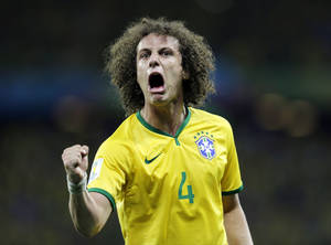 Photo - Brazil's David Luiz celebrates after scoring his side's second goal on a free kick during the World Cup quarterfinal soccer match between Brazil and Colombia at the Arena Castelao in Fortaleza, Brazil, Friday, July 4, 2014. (AP Photo/Natacha Pisarenko)