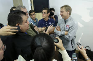 Photo - United States soccer coach Jurgen Klinsmann, right, speaks at a news conference for the World Cup soccer tournament in Stanford, Calif., Friday, May 23, 2014. (AP Photo/Jeff Chiu)
