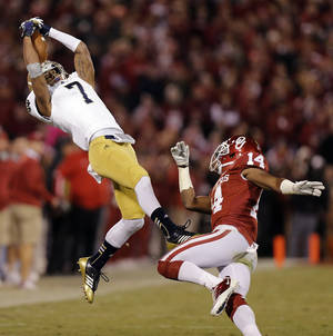 Photo - Notre Dame 's TJ Jones (7) makes a catch in front of OU's Aaron Colvin (14) during the college football game between the University of Oklahoma Sooners (OU) and the Notre Dame Fighting Irish at the Gaylord Family-Oklahoma Memorial Stadium on Saturday, Oct. 27, 2012, in Norman, Okla. Photo by Chris Landsberger, The Oklahoman