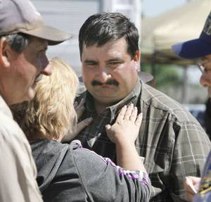 Photo - TORNADO / DEATH / CHILD / RECOVERY: Hank Hamil is comforted by a neighbor after hearing the news that the body of his missing three-year-old son Ryan Hamil had been found and recovered in Piedmont, OK, Thursday, May 26, 2011. Ryan has been missing since a tornado struck his family's home on Tuesday, May 24, 2011. By Paul Hellstern, The Oklahoman ORG XMIT: KOD