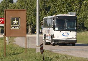 Photo -  One of several buses believed to be transporting immigrant children arrives Friday at Fort Sill in Lawton. Photo by Paul Hellstern, The Oklahoman.