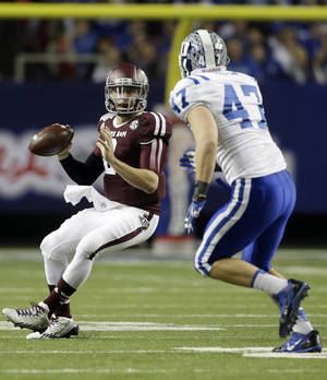 Photo - Texas A&M quarterback Johnny Manziel (2) is chased by Duke linebacker David Helton (47) in the first half of the Chick-fil-A Bowl NCAA college football game Tuesday, Dec. 31, 2013, in Atlanta. (AP Photo/John Bazemore)