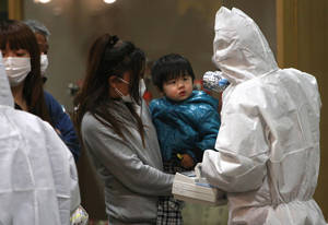 photo - FILE - In this March 15, 2011 file photo, a child is screened for radiation exposure at a testing center in Koriyama city, Fukushima Prefecture, Japan, after a nuclear power plant on the coast of the prefecture was damaged by March 11 earthquake. Experts and the government say there have been no visible health effects from the radioactive contamination from Fukushima Dai-ichi so far. But they also warn that even low-dose radiation carries some risk of cancer and other diseases, and exposure should be avoided as much as possible, especially the intake of contaminated food and water. Such risks are several times higher for children and even higher for fetuses, and may not appear for years. Okinawa has welcomed the people from Fukushima and other northeastern prefectures (states) affected by the March 11, 2011, earthquake and tsunami that set off the nuclear disaster. (AP Photo/Wally Santana,File)