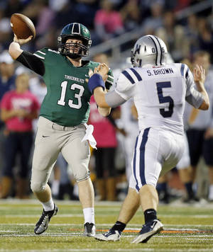 Photo - Norman North's Peyton Gavras (13) passes under pressure from Edmond North's Sam Brown (5) during a high school football game between Edmond North and Norman North in Norman, Okla., Thursday, Oct. 11, 2012. Photo by Nate Billings, The Oklahoman