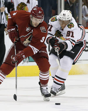 Photo - Phoenix Coyotes' Keith Yandle (3) tries to keep the puck away from Chicago Blackhawks' Marian Hossa (81) during the first period in an NHL hockey game, Friday Feb. 7, 2014, in Glendale, Ariz. (AP Photo/Ross D. Franklin)
