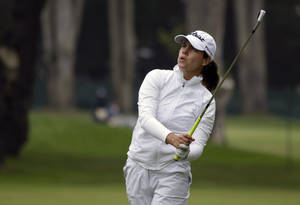 Photo - Karine Icher, from France, follows her shot from the first fairway of the Lake Merced Golf Club during the first round of the Swinging Skirts LPGA Classic golf tournament on Thursday, April 24, 2014, in Daly City, Calif. (AP Photo/Eric Risberg)
