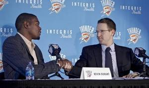 Photo - Kevin  Durant shakes hands with Thunder general manager Sam  Presti during a press conference to officially announce  Durant's five year contract extension to play of the Oklahoma City Thunder on Friday, July 9, 2010, in Oklahoma City, Okla. (AP Photo/The Oklahoman, Chris Lansberger)